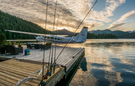 Float plane parked at Nootka Wilderness Lodge dock at sunset.