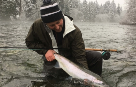 Person holding fish in water in winter.