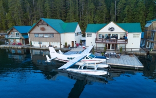 Small airplane with pontoons parked at dock of Nootka Wilderness Lodge.
