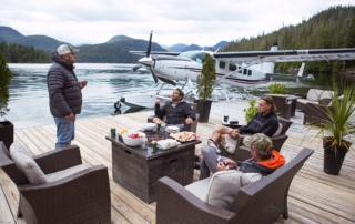 People enjoying a meal on the Nootka Wilderness Lodge dock patio.