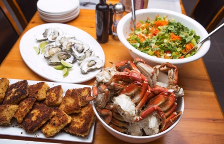 Assortment of prepared seafood and salad on dining table.