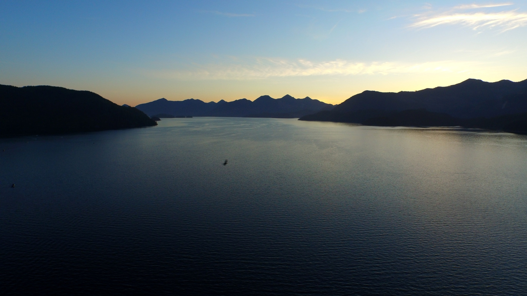 Nootka Sound surrounded by mountains at sunset.
