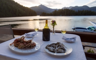 Seafood and wine on patio table with mountain and water backdrop at sunset.