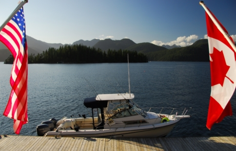 Fishing boat parked at Nootka Wilderness Lodge dock framed by Canadian and American flags.
