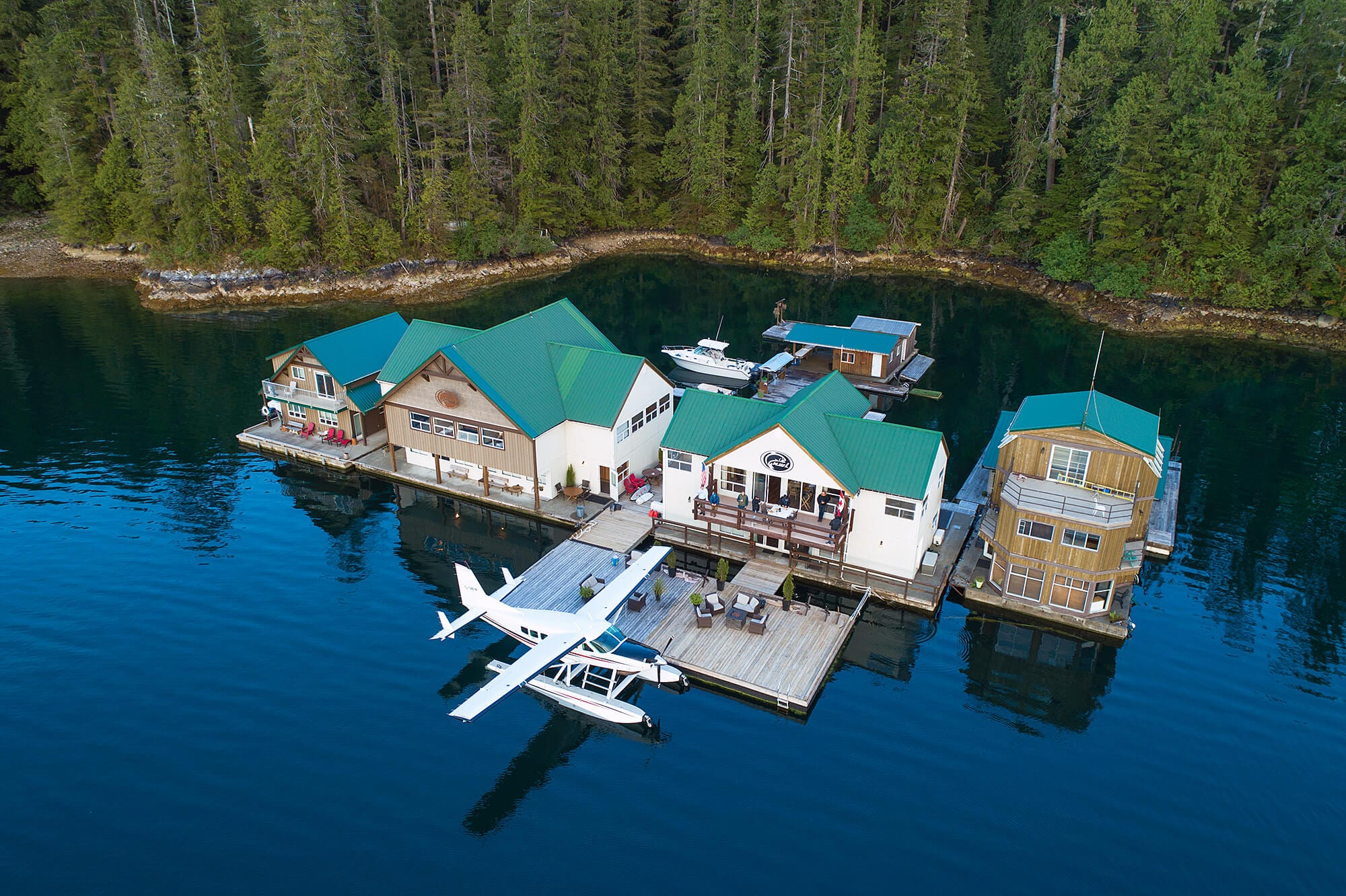Aerial view of Nootka Wilderness Lodge with float plane parked at dock.