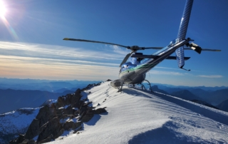 I helicopter waits atop a mountain.