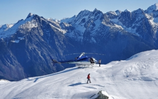 A helicopter tour group rests atop a mountain as two adventures gaze in awe at the scenic view.